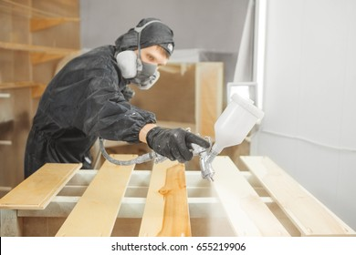 Man in respirator mask painting wooden planks at workshop.