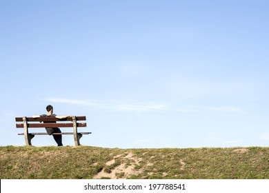 man resting alone  on a bench in an empty landscape