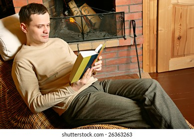 Man resting with book near fireplace