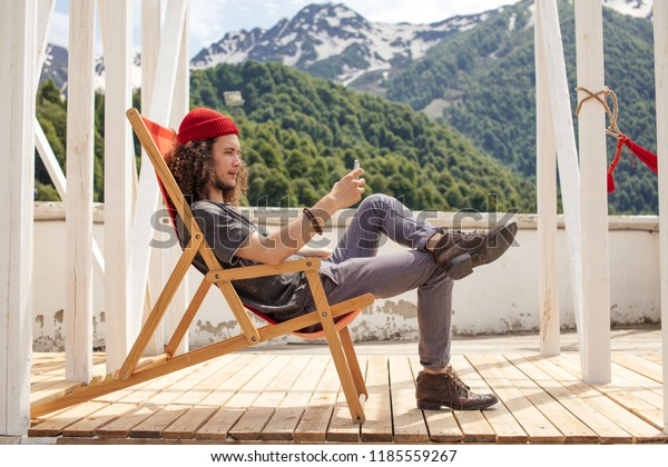 Man resting during hiking trip sitting on deck chair browsing smartphone