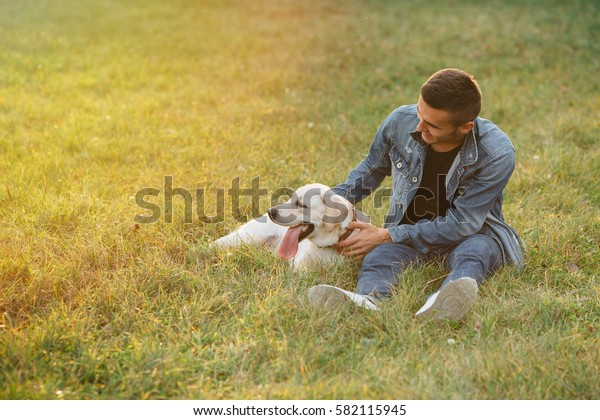 Man resting with his dog Labrador outdoors