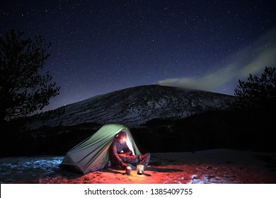 man resting in his illuminated tent on the snow under starry sky, on background Etna Mount, Sicily