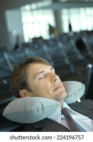 Man resting with neck pillow in airport lounge