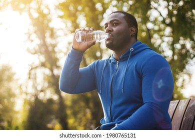 Man resting on bench after exercise and  drinking water .