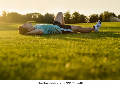Man resting on the grass after a marathon. Guy lying in the park at sunset.