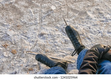 man resting on ice with focus on ice skates
