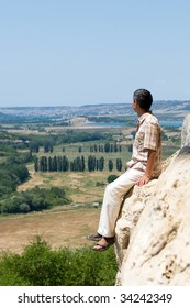 a man is resting on the mountain rock observing the distant valley