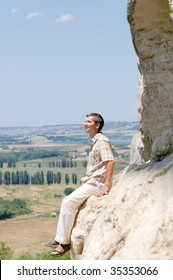 a man is resting on the mountain rock