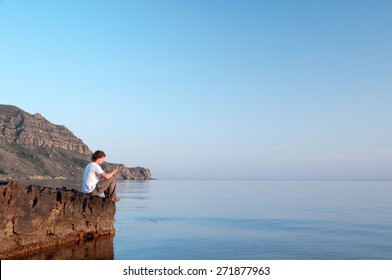 The man resting on the rock, sunset, sea.