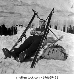 Man resting on snow between skis leaning on ski poles