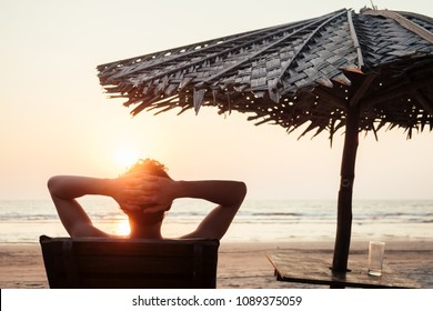 the man is resting on a sun lounger overlooking the sea and the sunset on the beach