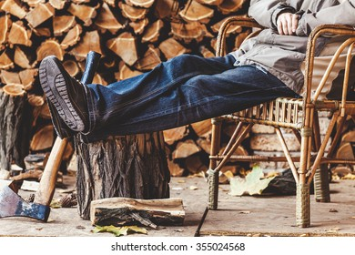 Man resting in a wicker chair and put his feet on a tree stump on a background of wood