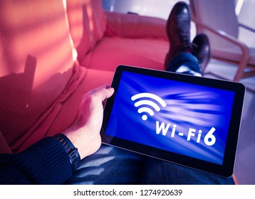 Man resting with wifi 6 words and icon on tablet screen..Wi-fi 6 is the next generation Wi-fi connectivity with high capacity, coverage and performance.