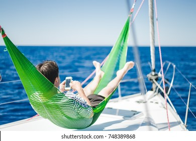 man rests in a hammock,yachting,resting,relax,man sleeping,man using phone,man reading messages,alone man,deck,summer holidays,attractive,happy,success,shirts,tan,amazing