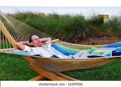 A man rests near the beach in a hammock.