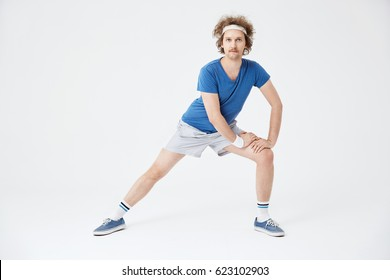Man in retro sportswear warming up muscles before working out