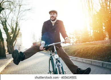 Man with retro styled bicycle enjoy sunrise cycling. Bearded guy having fun with bicycle