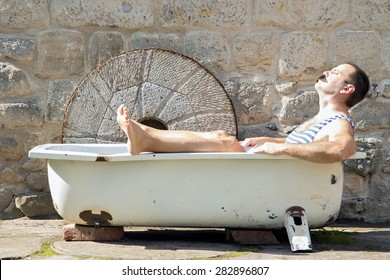 Man in retro swimsuit resting in the outdoor bathtub. Man in the old outdoor tub a sunbathe face.  Recreational relaxation in a swimsuit at the house.
