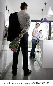 A man returning home to his family after work, holding a bunch of roses