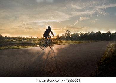 man ride bicycle for exercise on the way beside the lake at sunset