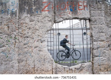 A man ride a bicycle pass the hole in section of ruined Berlin Wall