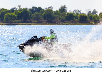 A man ride jet ski in the river with water splash.