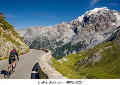 Man ride on bicycle from Famous Passo Dello Stelvio Climb. Italian - Swiss border, Alpen. Original sport wallpaper