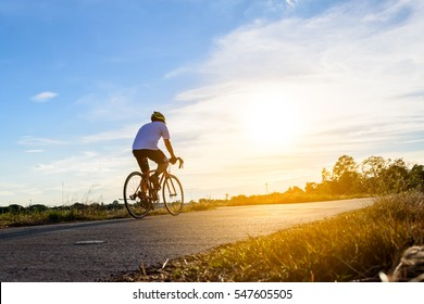 A man ride on bike on the road. Sport and active life concept sunset time. A man riding on  bicycle in a park. Blue sky with orange sun beam over the body of cyclist.