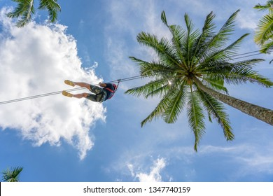 Man ride on zip line in the tropical jungle. Tourist ride on zipline in the rainforest of island Bali near rice terrase, Ubud, Indonesia