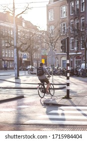 a man rides a bicycle in the road in Amsterdam in the rays of the sunset sun. Back view. Vertical