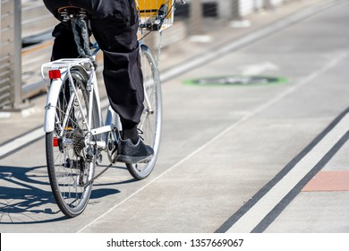 Man rides a bike on the bridge go to place of work preferring active healthy lifestyle and an alternative environmentally friendly mode of transport in order to preserve the environment of his city