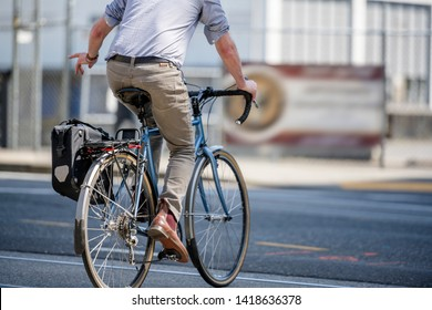 Man rides a bike on the street go to place of work preferring active healthy lifestyle and an alternative environmentally friendly mode of transport in order to preserve the environment of his city