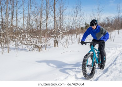 A man rides his fat bike on a trail in the snow.