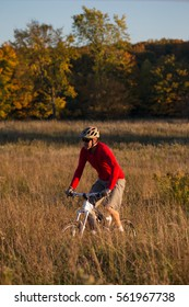 Man rides a mountain bike on single track trail during the autumn