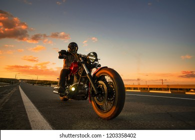 a man rides on the highway on a custom motorcycle at sunset. Stunning scenery when traveling