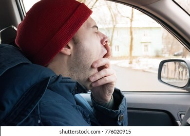 a man rides on the road in winter, a man yawns at the wheel, tired of driving