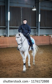 Man rides white horse at covered riding arena.