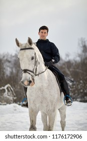 Man rides white horse outdoors on winter day.