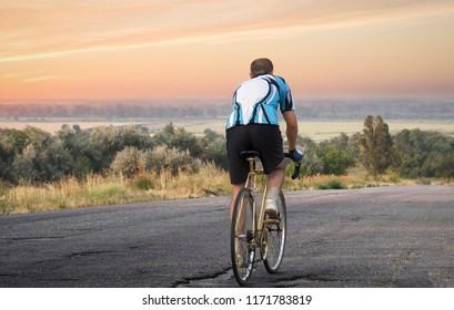 A man is riding along the highway on a bicycle, a beautiful sunset sky