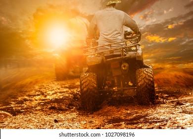 man riding atv through mud terrain field