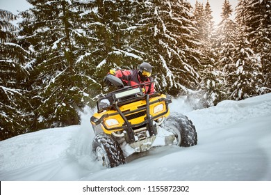 A man is riding an ATV in winter on the snow in his helmet.