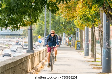 Man riding a bicycle. Budapest, Hungary - September 27, 2017: Front view, man riding a bicycle at an walk and cycle path in Budapest to avoid traffic. Trees, traffic and people in the background.
