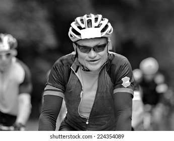 Man riding a bicycle close up in black and white.