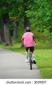 Man riding a bicycle in green summer park