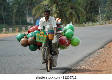 Man riding bicycle to market with load of plastic water jugs