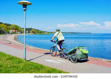 Man riding a bicycle. Nida resort town near Klaipeda in Neringa at the Curonian Spit and the Baltic Sea in Lithuania.