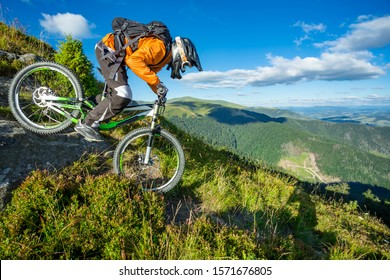 A man is riding bicycle, on the background of mountains and blue sky. Beautiful summer day.