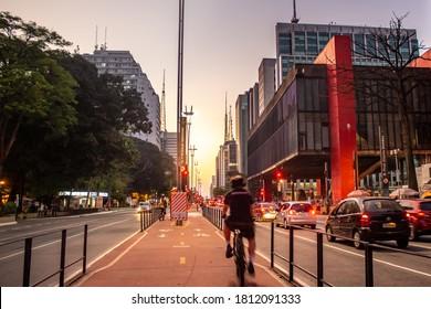 "Man riding a bicycle on the Paulista Avenue bike path  Translation: ""Next street. Peixoto Gomide street"""
