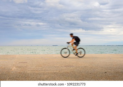 Man riding a bicycle on Thessaloniki quayside. Greece. motion blur