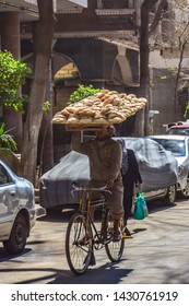 Man riding a bicycle while carrying a tray full of Egyptian bread over his head, Islamic Cairo, Egypt.
